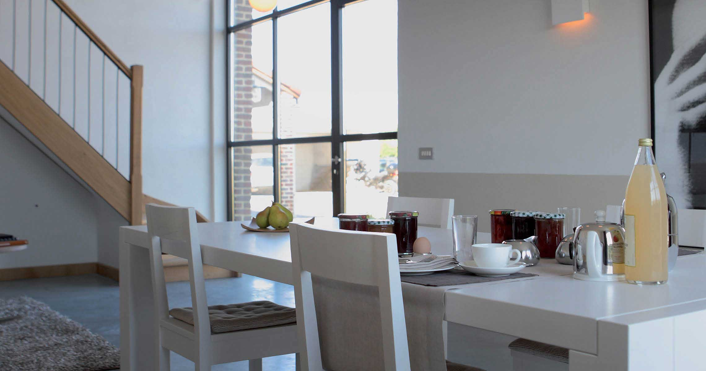 Breakfast table stairs and large window B&B Het Rooj